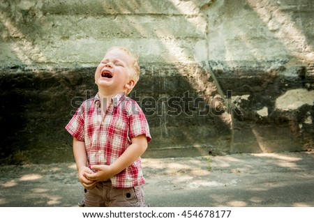 sad and unhappy child boy in the street is crying. Upset problem child with head in hands. concept for bullying, depression stress or frustration. concrete wall as  background