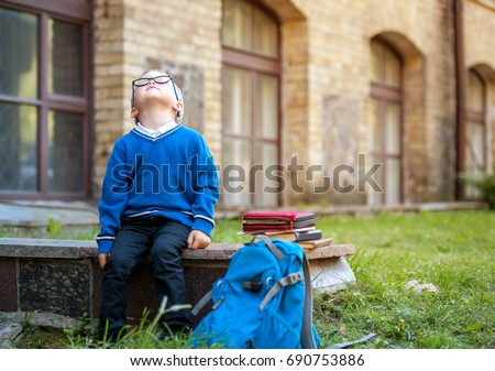 Sad and unhappy pupil with backpack. Upset toddler boy. problem child. concept for bullying, depression stress or frustration. On school background. Education for small kids.