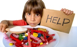 sad and vulnerable 4 or 5 years old female child asking for help  eating dish full of candy holding sugar spoon in sweet abuse dangerous diet and unhealthy nutrition concept isolated on white