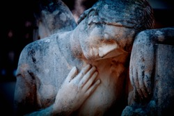 Sad angel on the tomb as symbol of death, pain and sorrow. Antique statue.