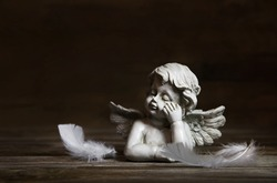 Sad angel with white feathers on a dark background for bereavement.