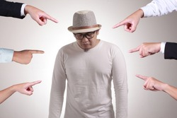 Sad anxious Asian man judged by different hands. Concept of accusation of guilty person, bully harrasment concept