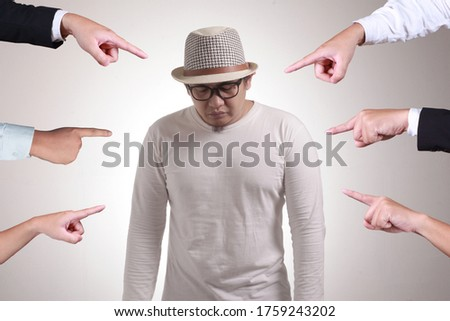 Sad anxious Asian man judged by different hands. Concept of accusation of guilty person, bully harrasment concept Foto stock ©