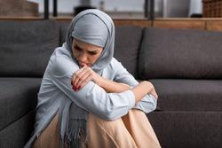 sad arabian woman in hijab sitting on floor in living room, domestic violence concept
