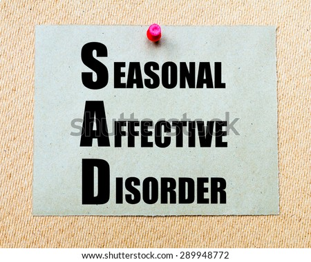SAD as Seasonal Affective Disorder written on paper note written on paper note pinned with red thumbtack on wooden board. Health conceptual Image