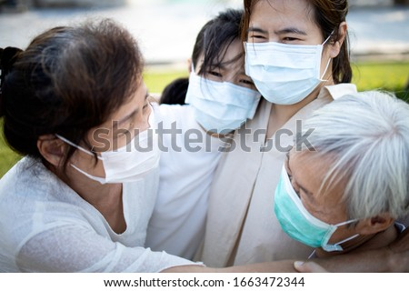 Sad asian family wearing medical mask crying,suffer from grief,great loss of her family infected,fight the Covid-19,Coronavirus outbreak,people affected epidemic crisis ,hug,comforting,encouragement
