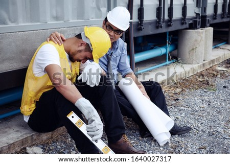 Sad Asian fired arab foreman cry while senior engineer manager cheer up at construction site. 2020 bad economy due to covid-19 or coronavirus pandemic positive. Layoff employees, Work from home.