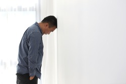 Sad asian man banging his head against a wall in office, copy space.