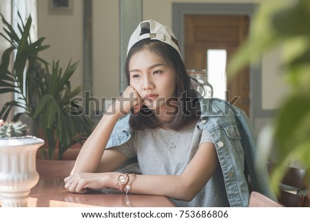 Sad asian women sitting in cafe,teenager female young woman sad depressed or thoughtful looking out of a window #753686806