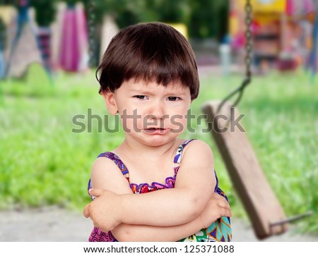 Sad baby girl crying in the park with the swing broken