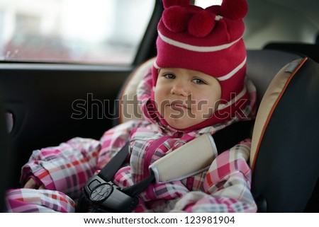 sad baby girl in car seat in winter time