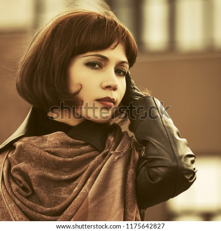 Sad beautiful fashion woman walking in city street Stylish female model with bob hair wearing black leather coat and brown scarf