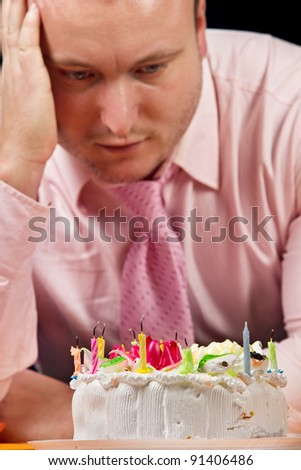 Sad birthday man with cake and candle