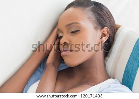 Sad black woman lying in a living room