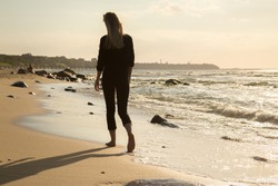sad blond barefoot woman walking away at sunny sea beach, toned image