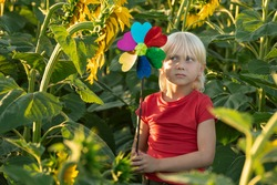 Sad blond boy with a toy windmill in his hands stands on a green field. Eco-friendly.