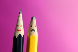 Sad blunt yellow pencil and smiling sharp black pencil. Concept develop yourself and positive attitude
