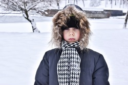 Sad boy in nature in winter. Winter concept. The kid walks in the fresh air. Cute boy in nature in winter.