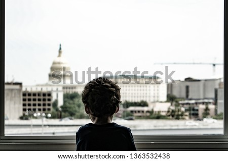 Sad boy in t shirt standing all alone near window and looking through the glass at the city outside. View from back.
