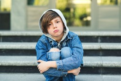 Sad boy is sitting on the stairs, before school. Alone unhappy child in city street. Bullying, depression, child protection or loneliness concept. Depressed teenage boy.