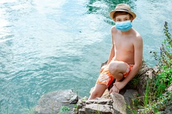 Sad boy looks into the distance on the lake beach in a protective mask, swimming trunks and hat. Fail of the tourist season. Coronavirus covid-19. Summer without travel. Disruption summer travel