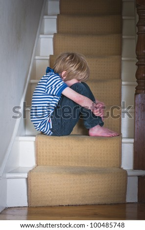 Sad boy on stairs - stock photo