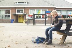 sad boy outside at schoolyard