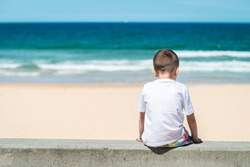 Sad boy sitting at he beach and thinking about something