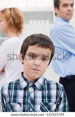 Sad boy staying in front of his parents whom are getting divorced