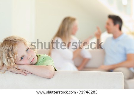 Sad boy with his arguing parents behind him - stock photo