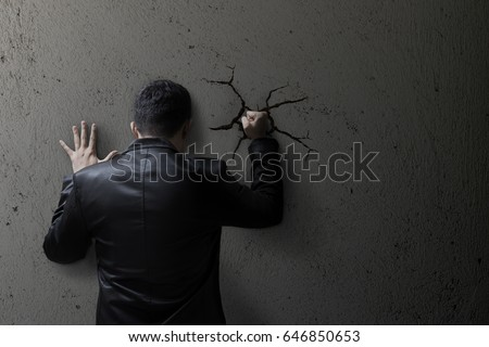 Sad business man feeling bad, hopeless, depressed, frustrated and repressed, Man hit the wall. Wall crack.