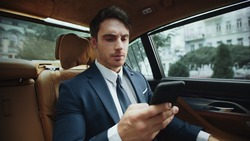 Sad business man receiving message on cellphone in business car. Elegant man looking at phone in automobile. Upset male professional reading bad news on smartphone in salon of modern car.