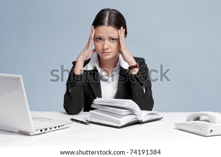 Sad business woman in office working with white table, laptop and diary personal organizer. Crisis!
