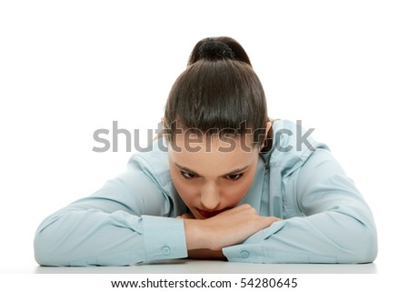 Sad business woman sitting behind the desk, isolated on white - stock photo