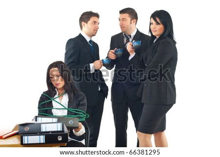 Sad business woman tied up in a chair at desk with many folders  working hard while her colleagues enjoy a business break and drinking coffee,conceptual image of  business woman slave of work