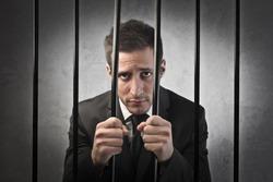 Sad businessman in prison