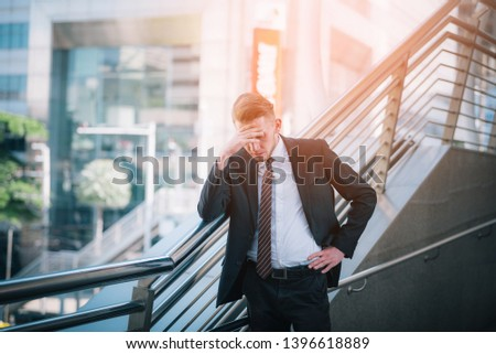 Sad businessman stressed and worried look down at outside office. Stress and worry concept.