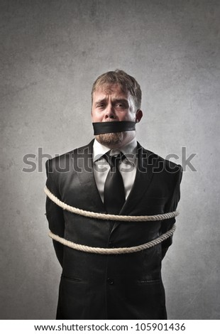Sad businessman tied and muffled