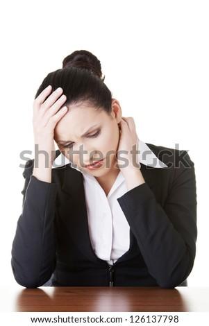 Sad businesswoman sitting behind the desk, isolated on white background