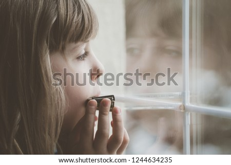 Sad Caucasian girl standing by the window and playing harmonica at home