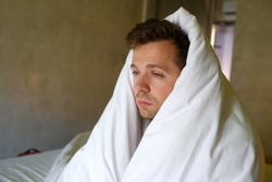 Sad caucasian man sitting on his bed with his head covered with blanket. Depression and troubles about life problems