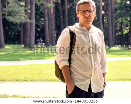 Sad caucasian 40 years man in the glasses, white shirt, outdor portrait, copy space