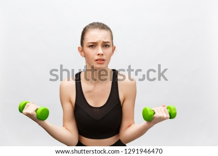 Sad Caucasian young woman with long medium brown hair in casual outfit holding dumbbell - Isolated #1291946470