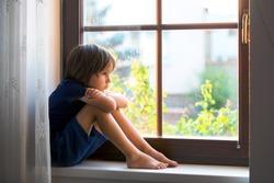 Sad child, boy, sitting on a window shield, watching the sunset