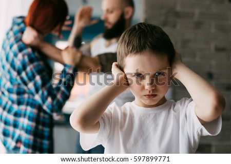 Sad child covering his ears with hands during parents quarrel. Man about to beat his wife #597899771