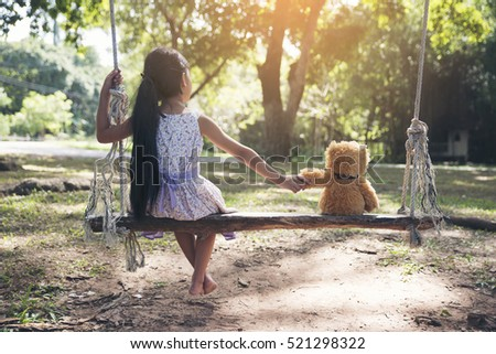 Sad child holding hand with teddy bear on wooden swing in park.Asian little girl sitting with best friends forever,sad moment.Teddy Bear is a gift,toy and best friend for children.Friendship concept.