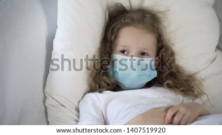 Sad child in medical face mask lying in bed, suffering rare disease, epidemic Stockfoto ©