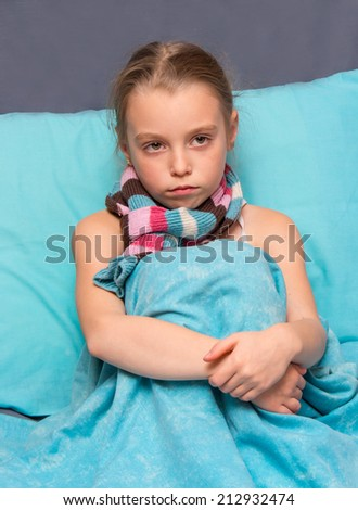 Sad child is sitting on the bed.