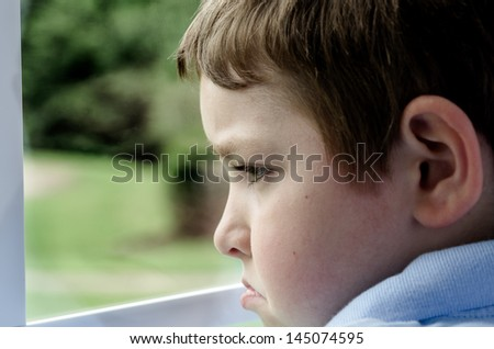 stock-photo-sad-child-looking-out-window-on-gloomy-day-145074595.jpg