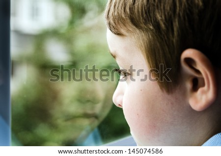 Sad child looking out window with reflection on gloomy day